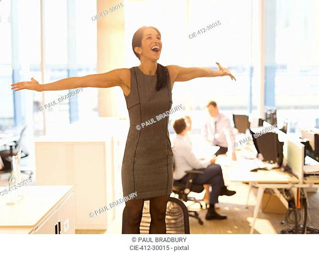 Exuberant businesswoman celebrating with arms outstretched on top of chair in office
