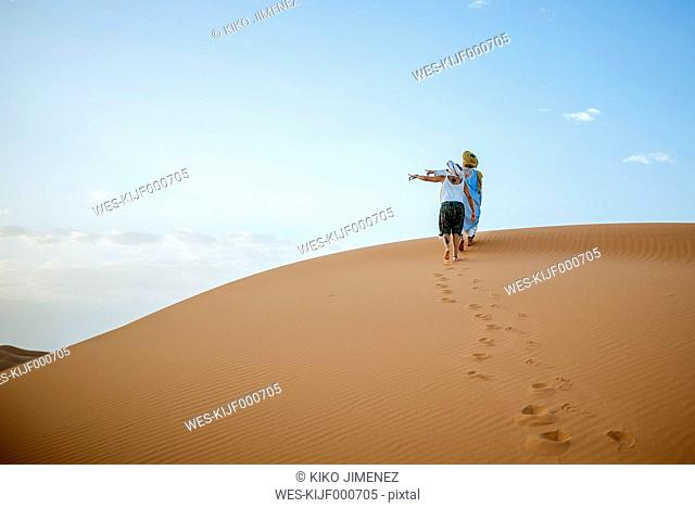 Berber man and woman tourist walking in the desert, pointing to the left
