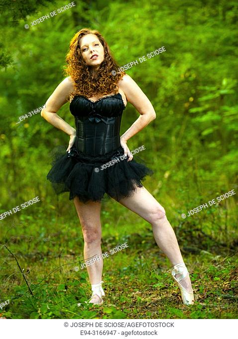 A pretty 39 year old redheaded woman wearing a black corset and a tutu looking at the camera, outdoors