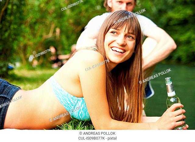 Couple relaxing in park, young woman holding glass bottle
