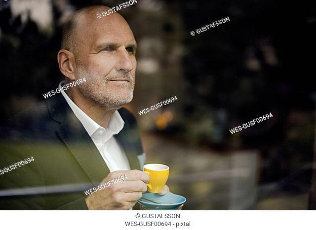 Senior businessman standing by window, drinking coffee