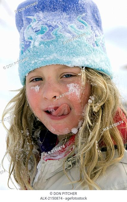 Close Up Of Young Girl Licking Snow Off Of Face While Sledding At Ohlson Mountain Near Homer, Alaska
