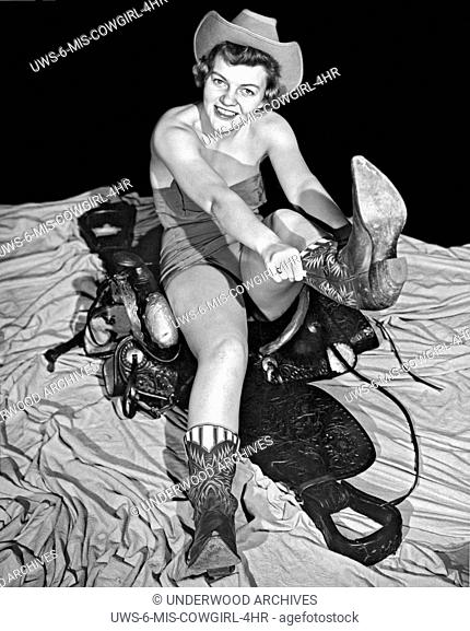 Texas: 1954. .A pretty young woman sitting on a saddle while wearing a bathing suit and a Stetson hat pulls on her cowboy boots