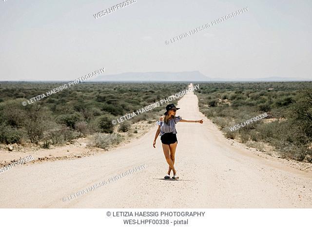 Namibia, woman hitchhiking on the road to Spitzkoppe