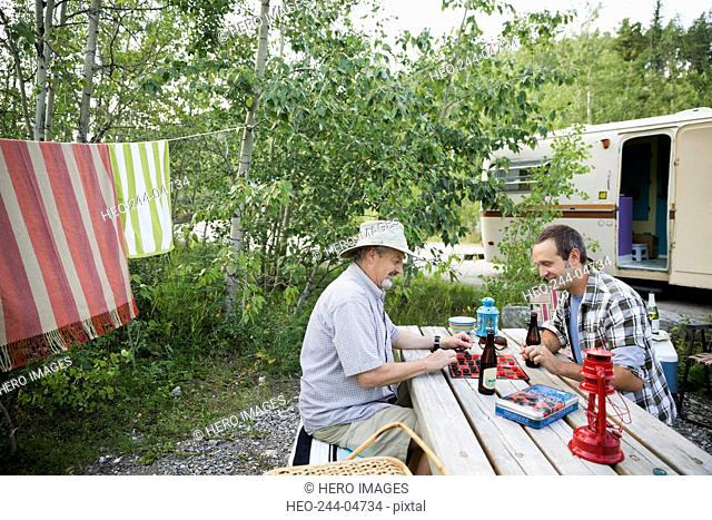 Father and son drinking beer playing checkers campsite