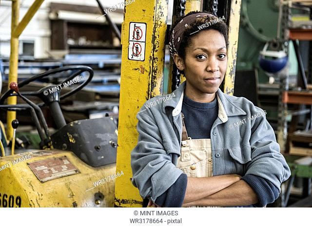 Black woman factory worker and a fork lift in a sheet metal factory