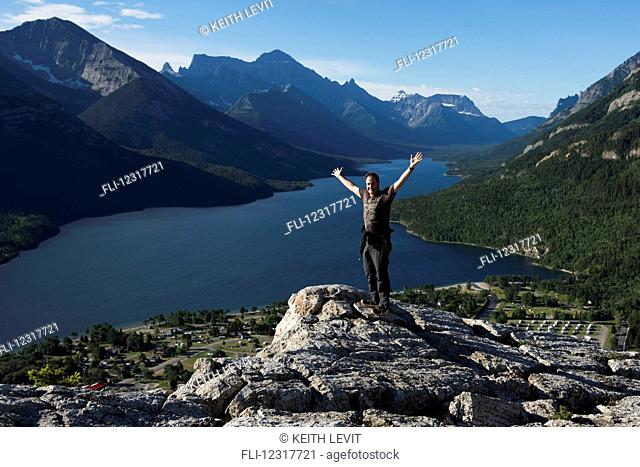 A man stands on a rocky ridge overlooking a lake and mountains in Waterton Lakes National Park; Alberta, Canada