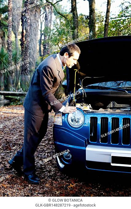 Businessman examining a broken down car