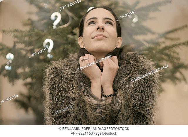 woman looking up searching for answer and inspiration, in front Christmas tree with lights of question marks, faith, hope, in Munich, Germany