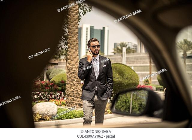Car window view of businessman talking on smartphone outside hotel, Dubai, United Arab Emirates
