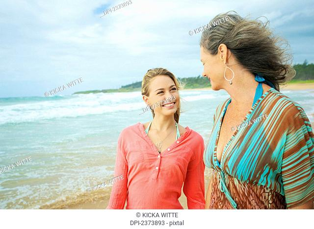 A mother and daughter walking together on the beach at the water's edge; Kauai, Hawaii, United States of America