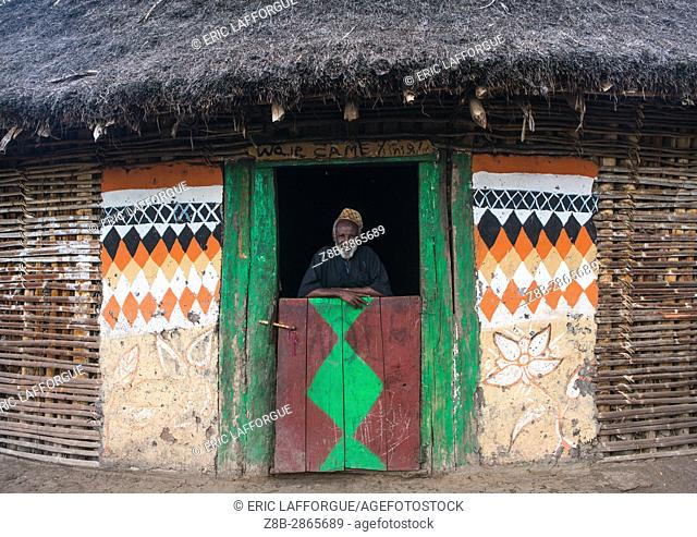Ethiopian muslim man standing in front of his traditional painted house, Kembata, Alaba Kuito, Ethiopia