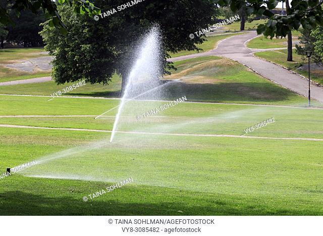 Sprinklers in park water the grass on a hot day of summer in Finland