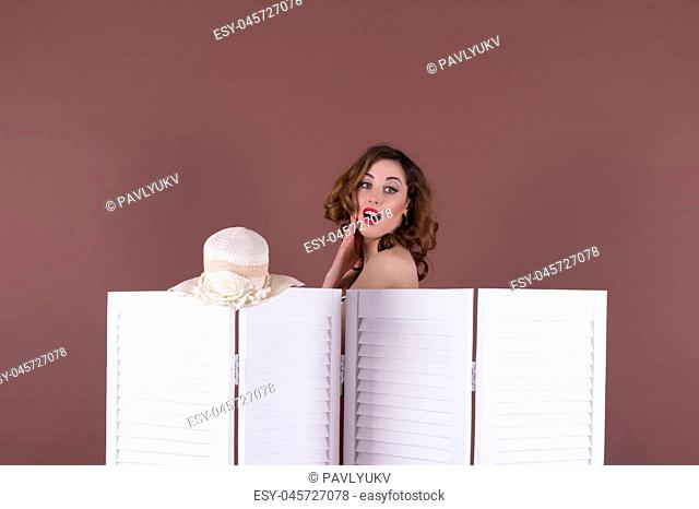 Surprised woman looking behind the folding screen