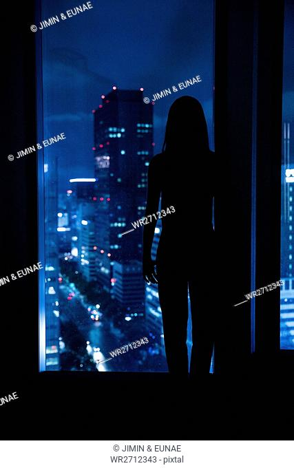 Silhouette of young woman at night