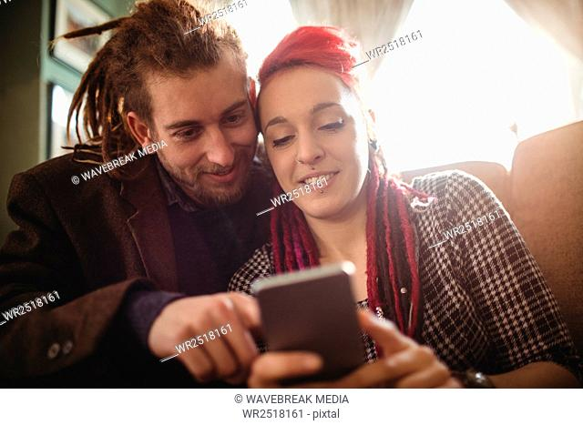Happy hipster couple using mobile phone