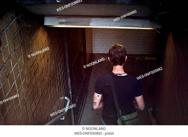 USA, New York City, Man walking down steps of Metro station