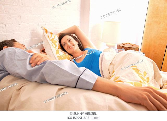 Mid adult couple relaxing in bed