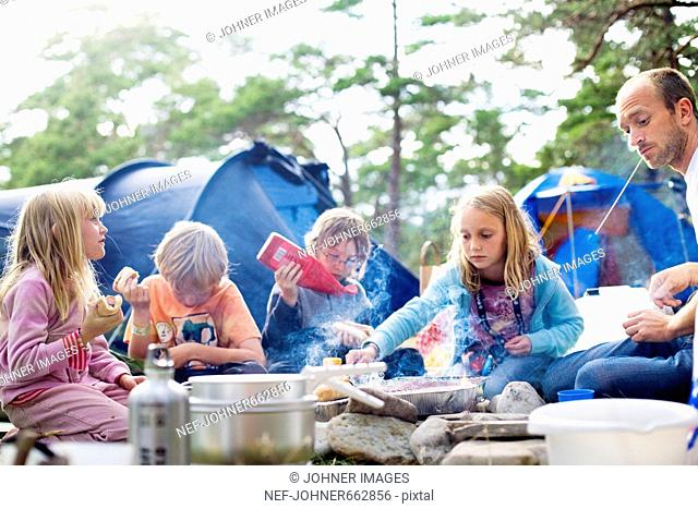 A family eating food outside a tent, Sweden