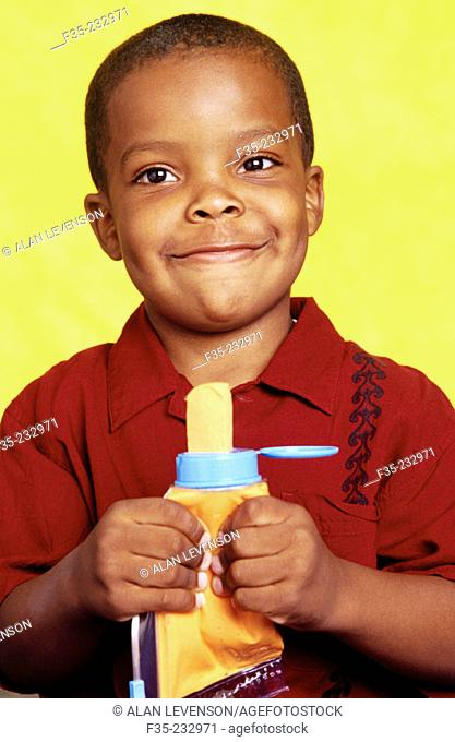 Young boy squeezing tube of yellow play material