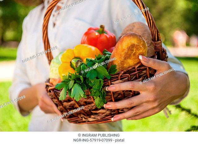 Vegetables in hands. Unrecognizable woman holding basket full of natural organic food - vegetables and bread outdoors