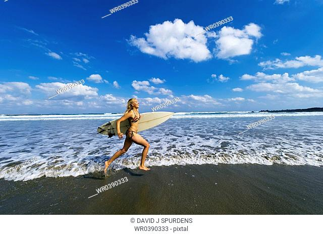 A young surfer runs home after a days surfing in the Ocean