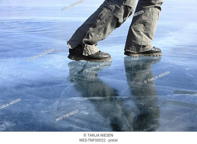 Russia, Lake Baikal, person on frozen lake, low section