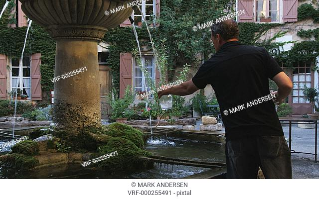 man filling up water jars from a fountain