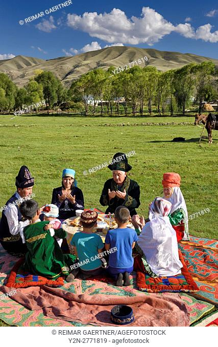 Kazakh family in traditional clothes praying before a picnic meal in pastureland at Saty Kazakhstan