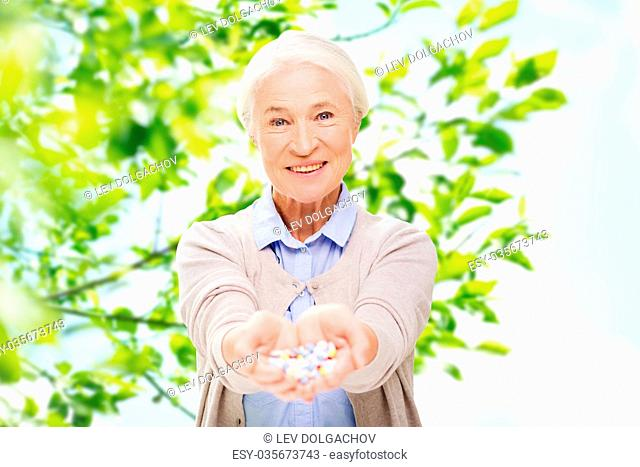 age, medicine, health care and people concept - happy senior woman with pills over green natural background
