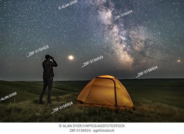 A Park interpreter poses for a scene in Grasslands National Park, Saskatchewan, of stargazing with binoculars under the Milky Way on a dark moonless night