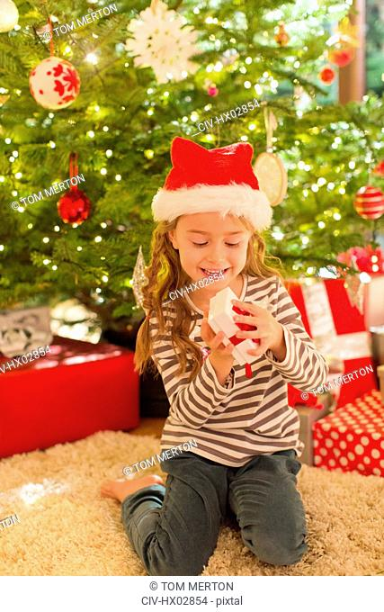Smiling girl in Santa hat opening gift in front of Christmas tree