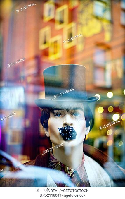 Male mannequin with a top hat and his mouth covered with an adhesive paper, seen through glass with a city reflections. London, England, UK, Europe