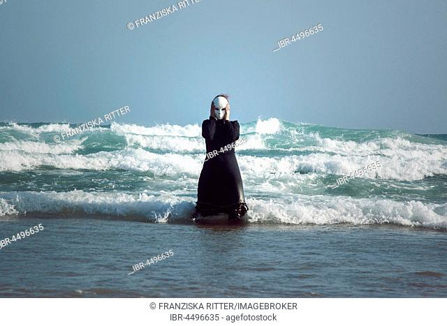 Woman in black dress with mask, standing in the surf in the sea