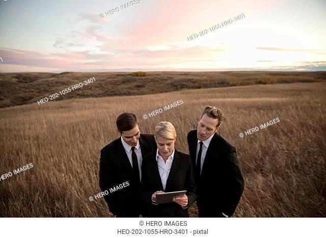 Business people using digital tablet in field