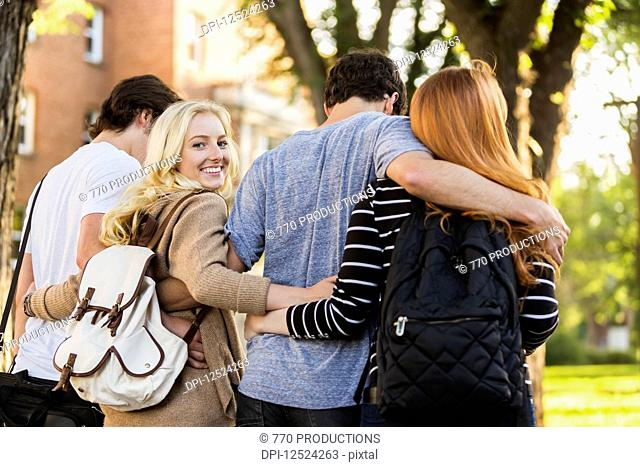 Four friends walking and talking in an embrace on the university campus with a female looking back at the camera; Edmonton, Alberta, Canada