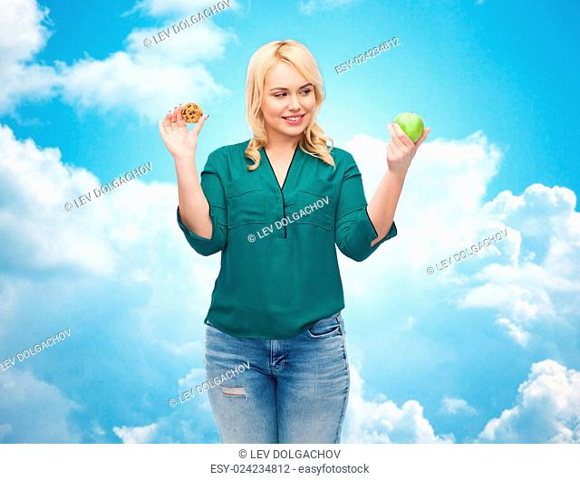 healthy eating, junk food, diet and choice people concept - smiling woman choosing between apple and cookie over blue sky and clouds background