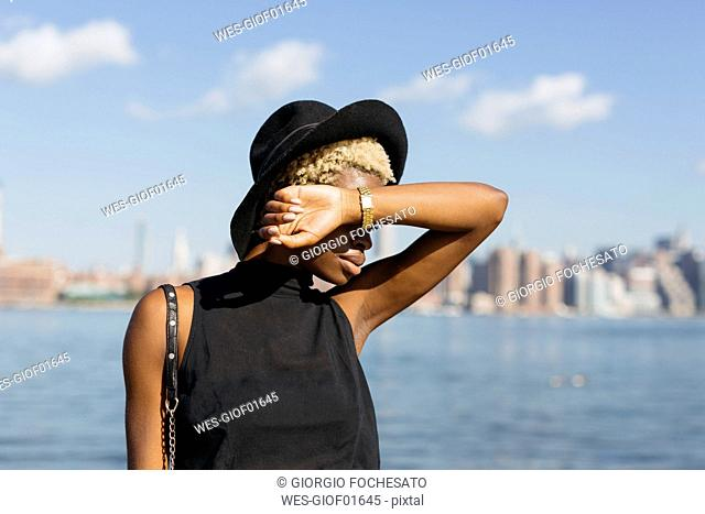 USA, New York City, Brooklyn, young woman at East River wearing a hat