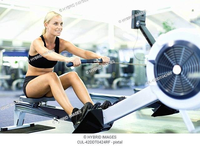 Woman using rowing machine in gym