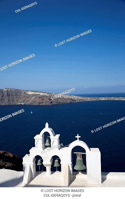 View of sea and white washed church bell tower, Oia, Santorini, Cyclades, Greece