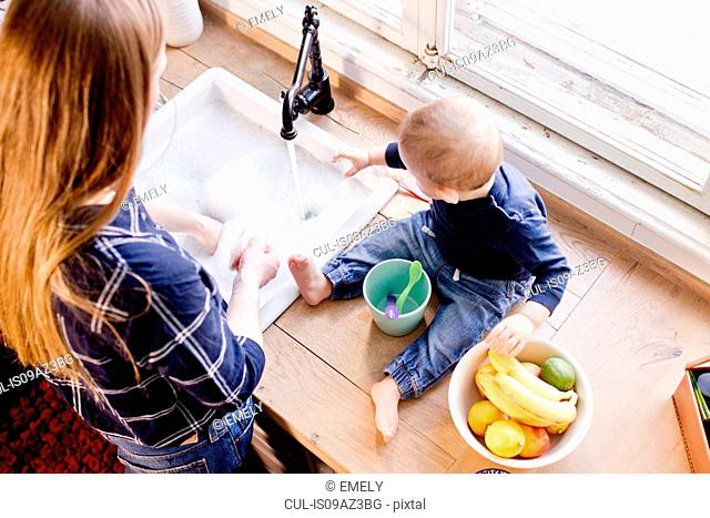 Overhead view of woman at kitchen sink with baby son