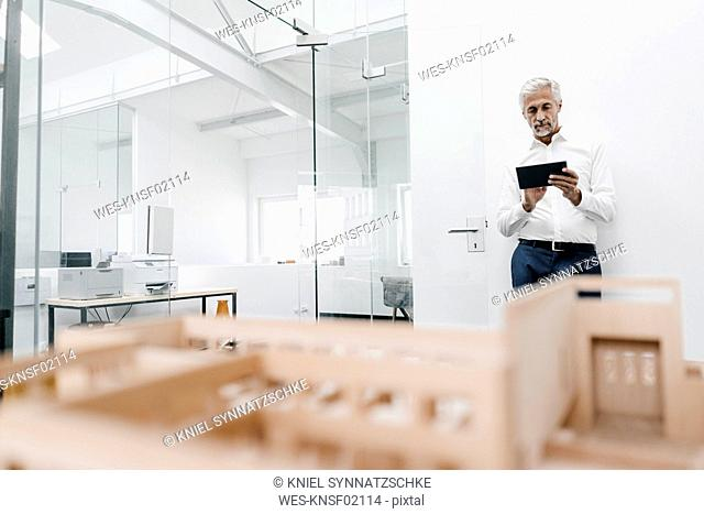 Mature businessman with architectural model and tablet in office