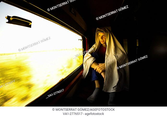 A young man on a lonely journey through the desert of Rajasthan, looks at the world from the train window