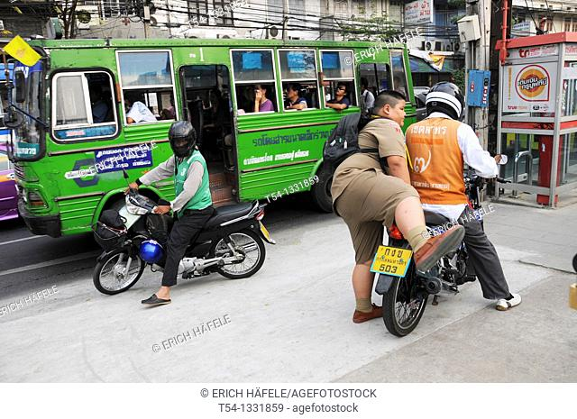 Thick Thai schoolchildren is rising on a motorcycle taxi