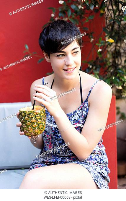 Smiling young woman drinking a cocktail in pineapple outdoors