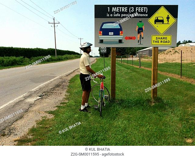 A cyclist looks at an Illustrated share the road sign, Ontario Canada. Recommends space of one meter between cars and cyclists