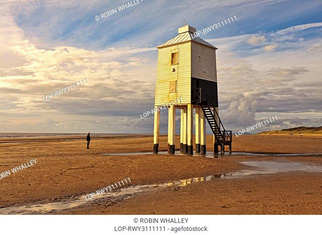 England, Somerset, Burnham-On-Sea. A man standing on the beach looking at Burnham-on-Sea Low Lighthouse, built by Joseph Nelson in 1832