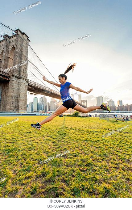 Young woman training in front of Brooklyn bridge, New York, USA