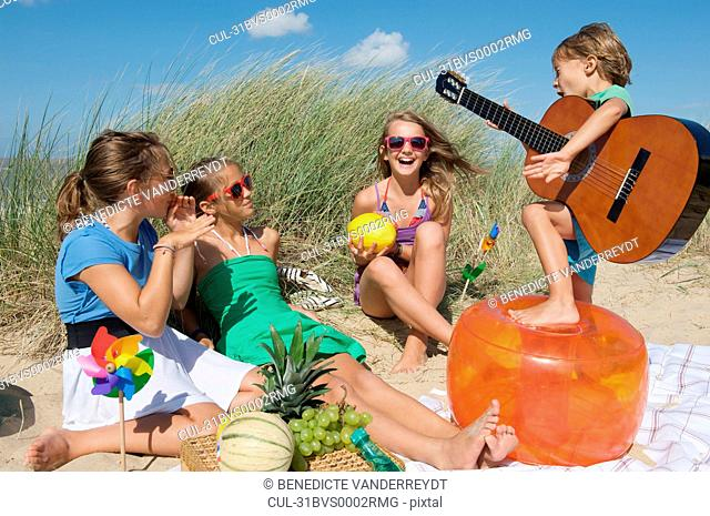 Child playing guitar for girls