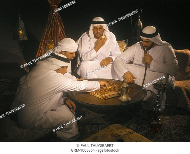 Arab men playing backgammon in Arabian tent